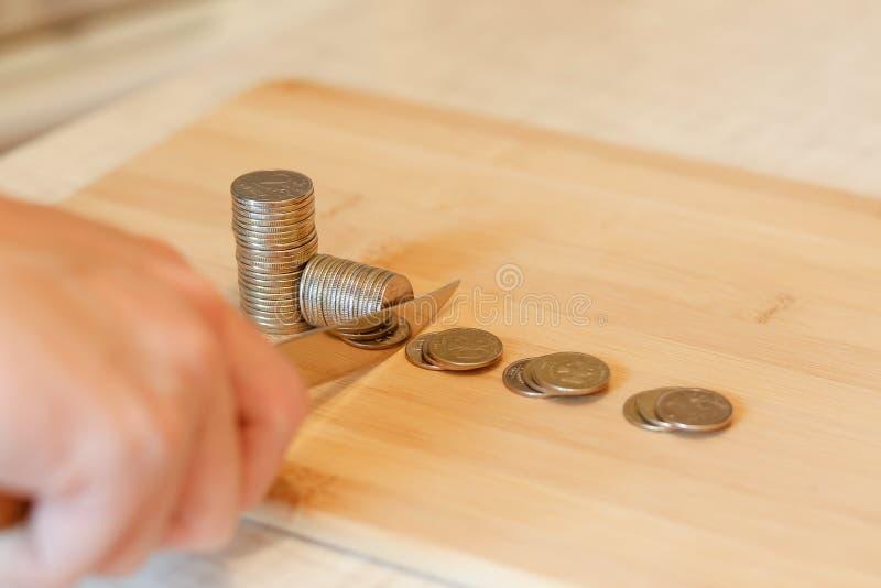 Hand mit einem Messer, das einen Stapel der Münze schneidet Konzept von Etatverkürzungen lizenzfreie stockbilder