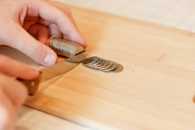 Hand mit einem Messer, das einen Stapel der Münze schneidet Konzept von Etatverkürzungen stockbilder