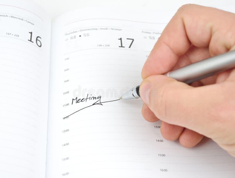 Hand mit einem Stift und einem Zeitplan lizenzfreie stockbilder