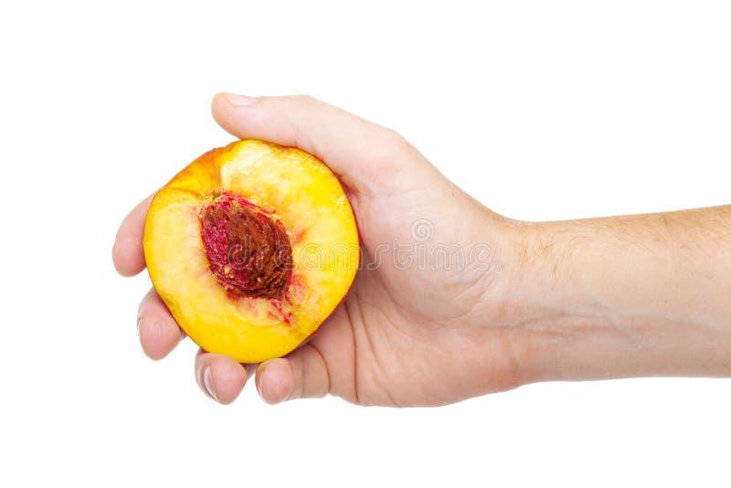 Hand mit einer neuen saftigen Pfirsichspalte zur Hälfte lokalisiert auf einem Weiß lizenzfreies stockfoto