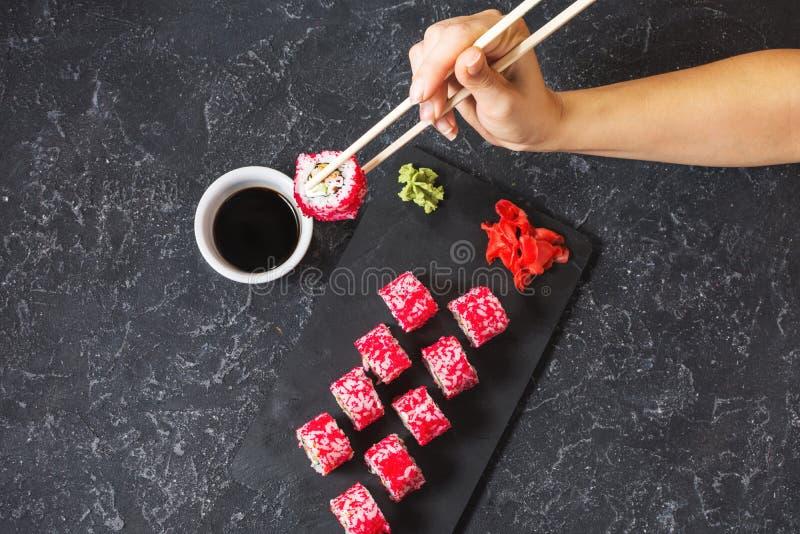 Hand mit Essstäbchen auf den Sushi eingestellt mit Sojasoße auf schwarzem Steinschreibtisch stockfoto