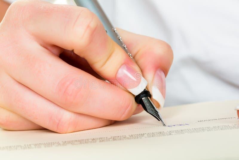 Hand mit Füllfederhalter schreibt unter Vertrag lizenzfreie stockfotos