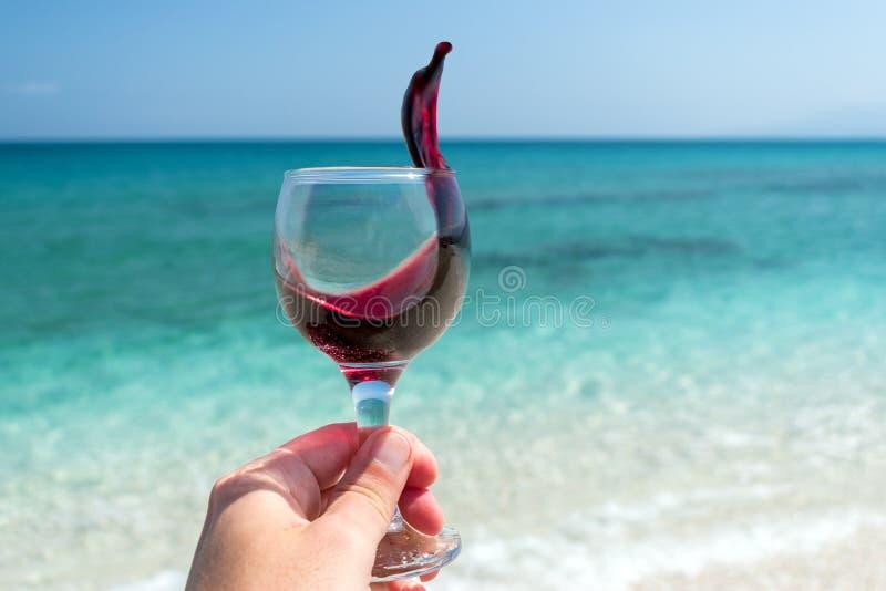 Hand mit Glas Rotwein auf dem Strand am sonnigen Tag des Sommers lizenzfreie stockfotografie