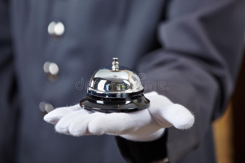 Hand mit Hotelglocke lizenzfreie stockfotos