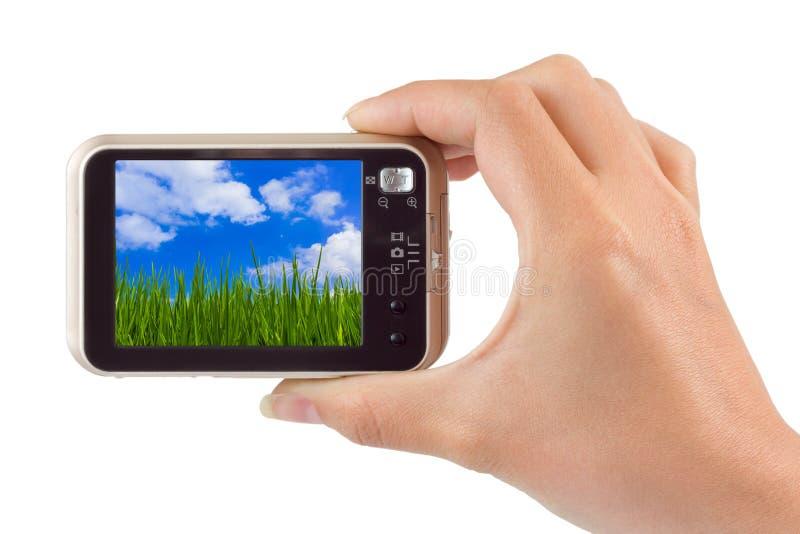 Hand mit Kamera und Gras und bewölkter Himmel mein Foto lizenzfreie stockfotos