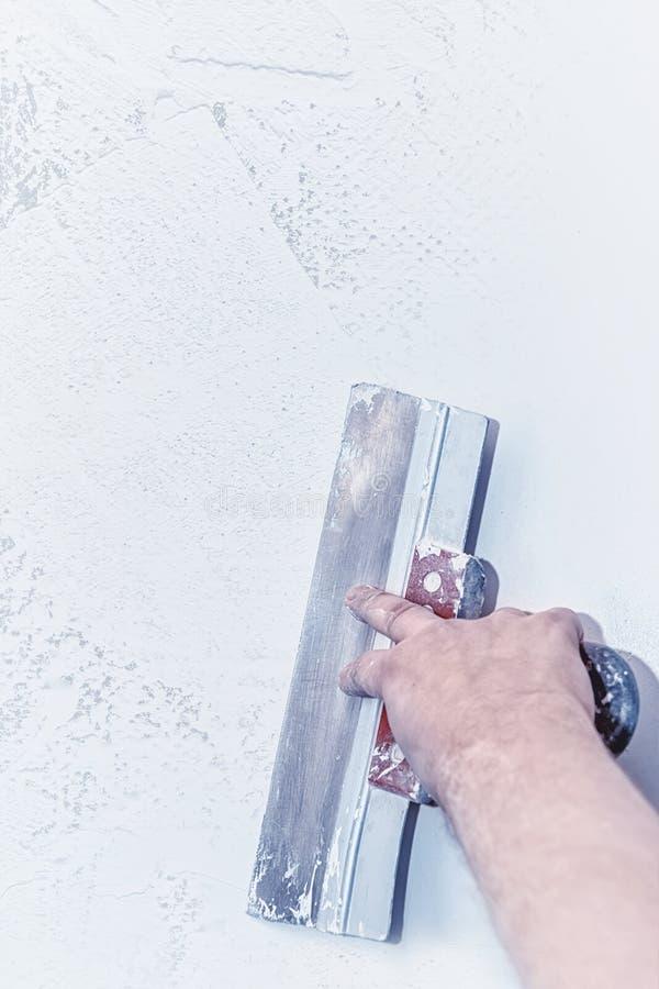 Hand mit Kelle, Reparaturwand, Kelle mit Kittstruktur, der Prozess des Anwendens einer Schicht der Kelle, Arbeit mit Kitt Kopiere lizenzfreies stockbild