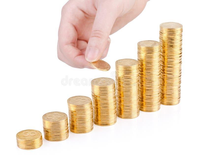 Hand mit Münze und Spalten von den Goldmünzen lokalisiert stockfotos