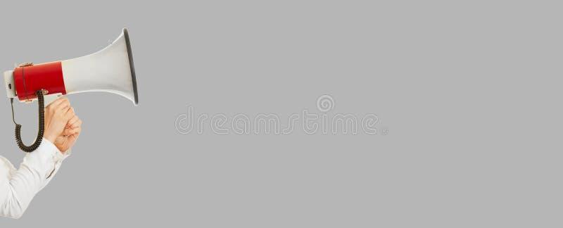 Hand mit Megaphon als Hintergrundfahne lizenzfreie stockfotos