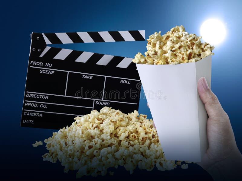 Hand mit Popcorn, Film clapperboard, an am blauen Hintergrund lizenzfreie stockfotografie