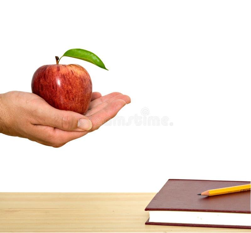 Hand mit rotem Apfel und Buch lizenzfreie stockbilder