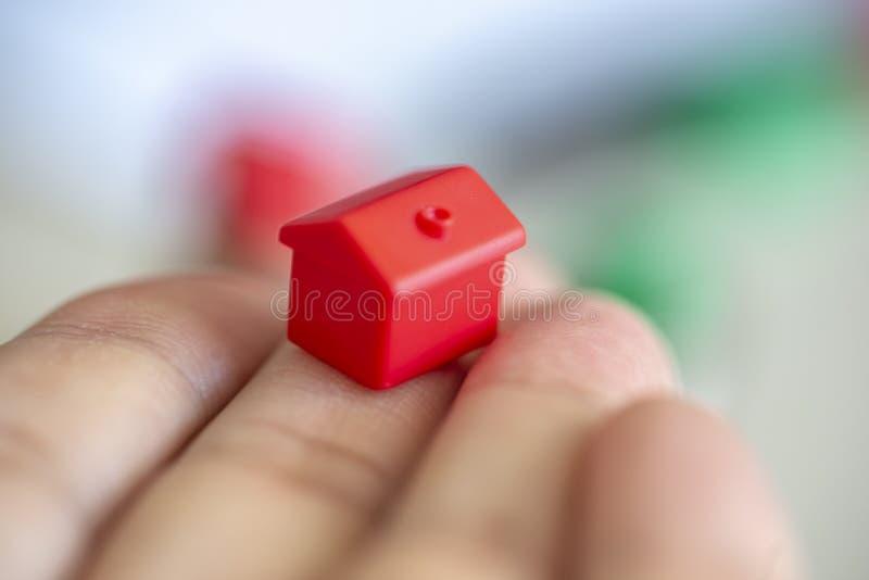 Hand mit rotem Miniaturhaus lizenzfreie stockbilder