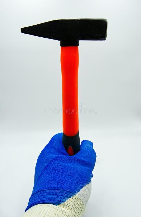Hand mit Schutzhandschuh hält einen Hammer auf weißem Hintergrund stockfoto