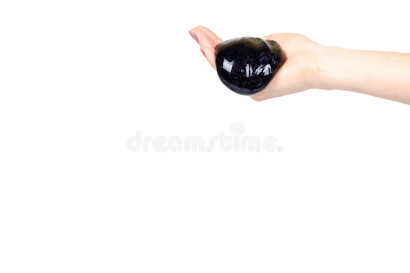 Hand mit schwarzem Schlammspielzeug f?r Kinder, Funkeln und Schmiere lizenzfreie stockfotografie