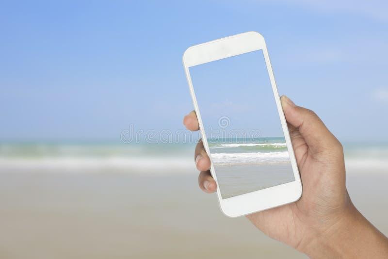 Download Hand Mit Smartphone Mit Tropischem Meer Und Strand Stockfoto - Bild von schönheit, ausrüstung: 106801346