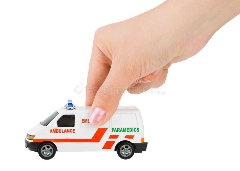 Hand mit Spielzeugkrankenwagenauto lizenzfreie stockbilder