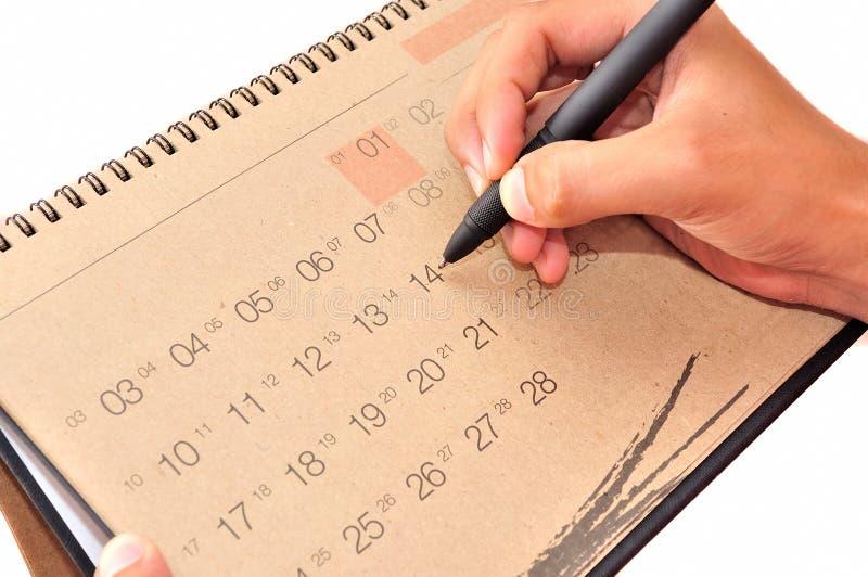Hand mit Stift nehmen eine Kenntnis in Kalender lizenzfreie stockfotos