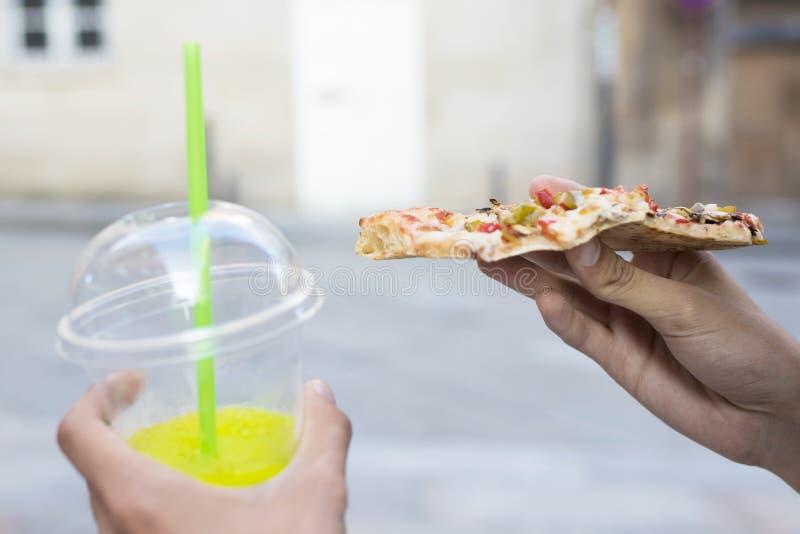 Hand mit Teil Pizza und Soda lizenzfreie stockfotos
