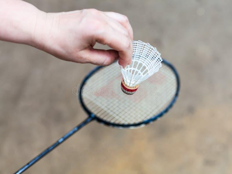 Hand mit weißem Federball über Federballschläger stockbild