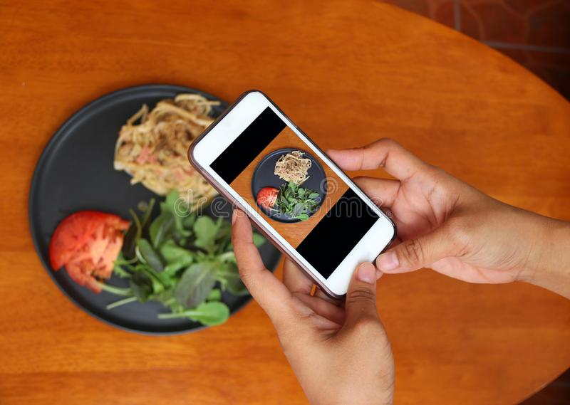 Hand with mobile phone take a photo of the The Spaghetti Carbonara with green vegetable in the black dish. Hand with mobile phone take a photo of the The stock photo