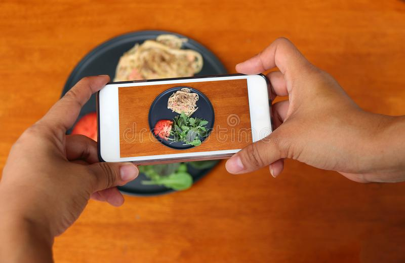 Hand with mobile phone take a photo of the The Spaghetti Carbonara with green vegetable in the black dish. Hand with mobile phone take a photo of the The stock image