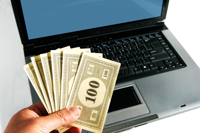 Download A Hand With Money In Front Of A Computer Stock Photo - Image: 13127070