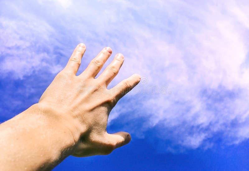 Hand mot himlen och molnen, handen som når för himlen, begreppsmässigt foto arkivbilder