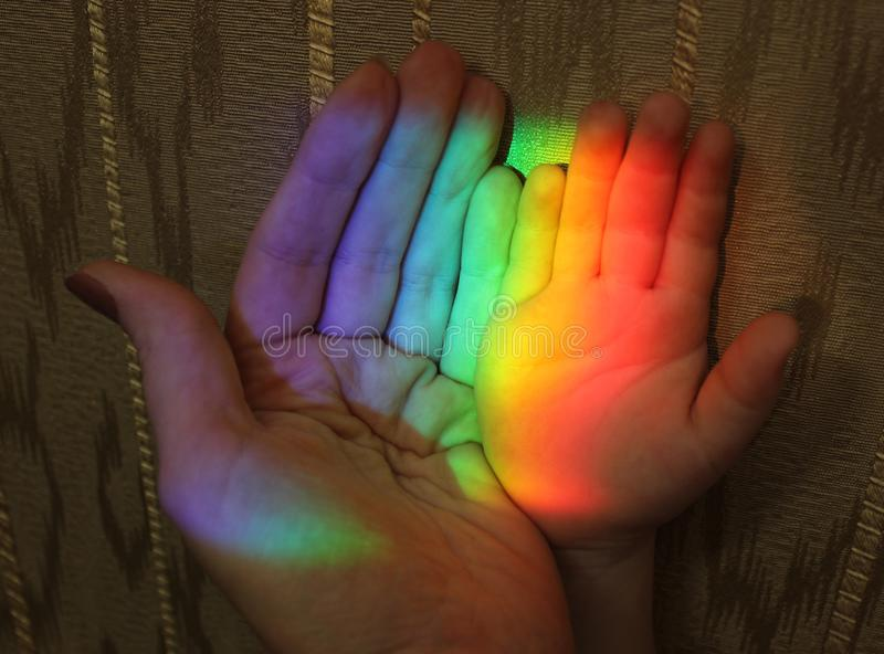 Hand of mother and child rainbow stock photography