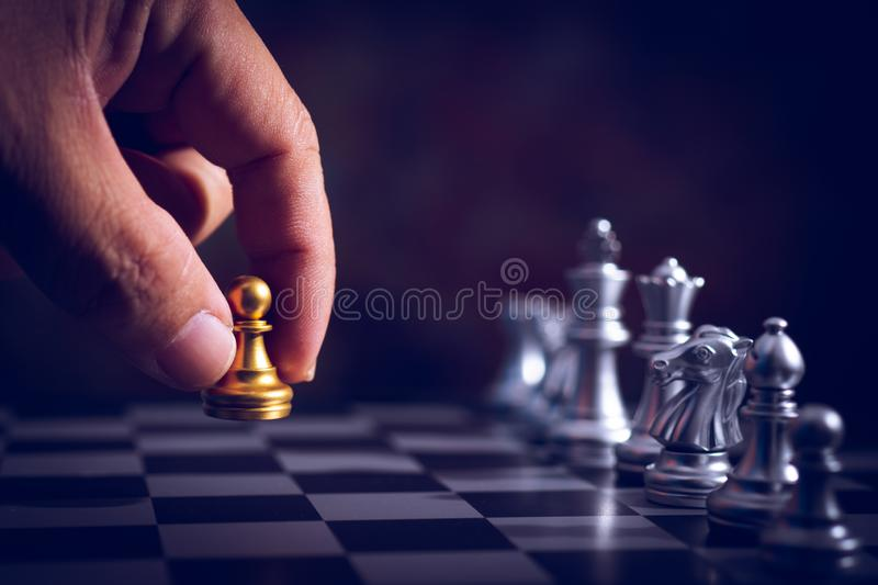hand move back rank of chess boad game to practice planing and stratagy, business thinking concept stock photography