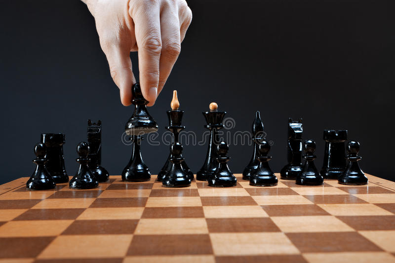 Hand moves chess pawn. On a dark background royalty free stock images