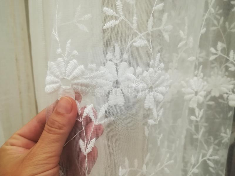 Hand moves a curtain. Spying from the window royalty free stock image