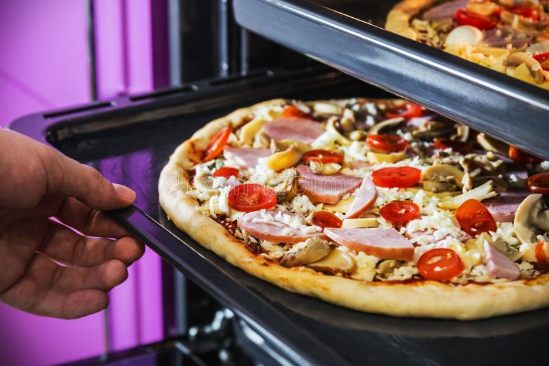 Hand moves the tray of pizza with mushrooms, ham and mozzarella. Cooked baking in the oven stock images