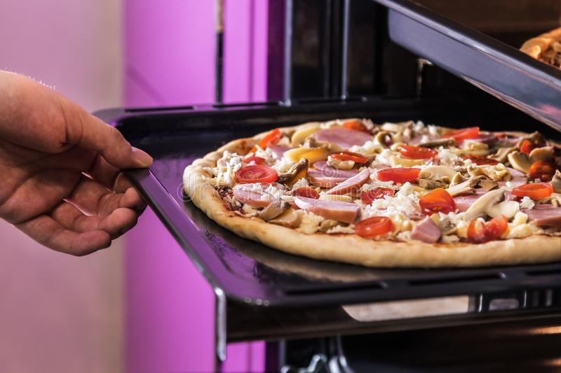 Hand moves the tray of pizza with mushrooms, ham and mozzarella. Cooked baking in the oven royalty free stock photography