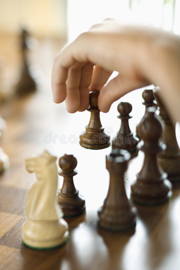 Hand moving chess piece. royalty free stock photos