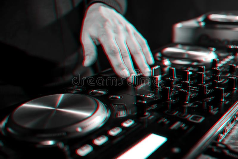 Hand moving of DJ controllers on music control panel in night club. Hand moving of the DJ controllers on the music control panel in night club. Black and white royalty free stock image