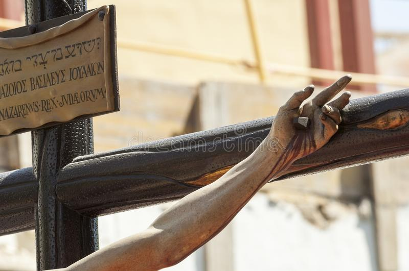 Hand nailed to the cross of the sculpture of the crucified Chris stock photo