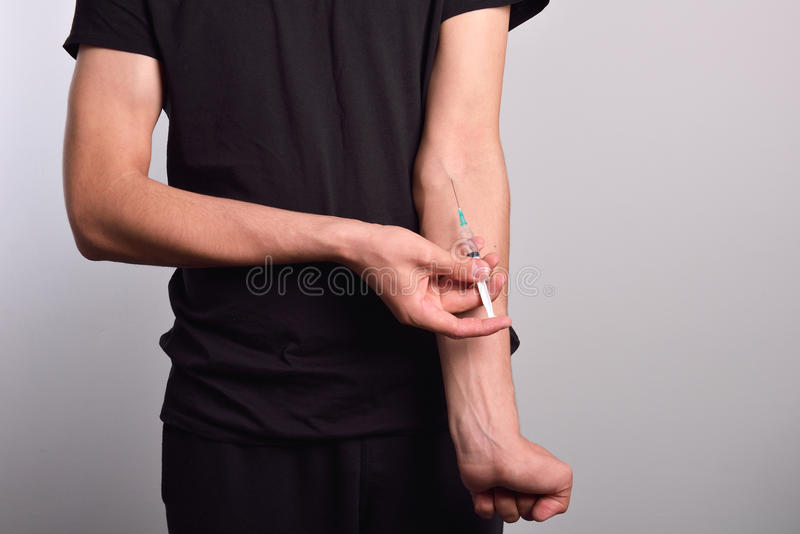 Hand of narcotist preparing to inject drugs royalty free stock image