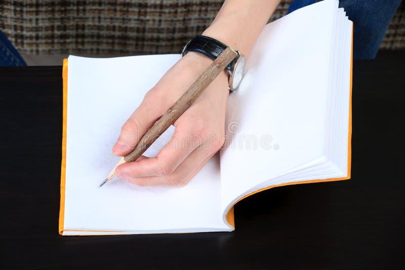 Hand and notebook. Close up stock photos