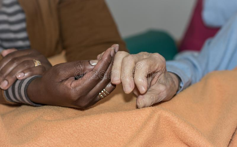 Hand of nurse holding a senior woman. Concept of helping hands, care for the elderly stock images