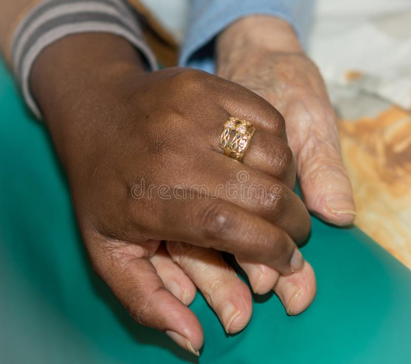 Hand of nurse holding a senior woman. Concept of helping hands, care for the elderly royalty free stock images
