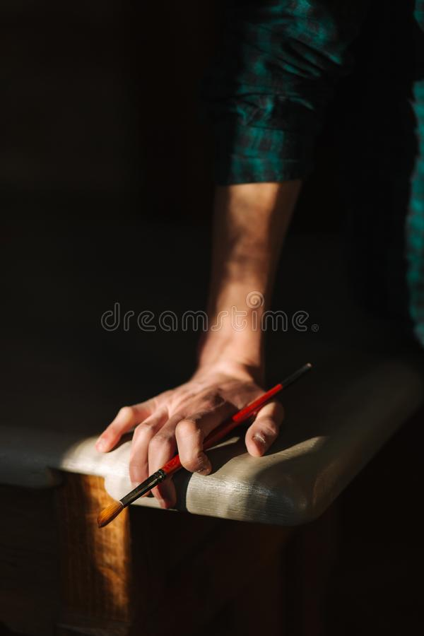 Hand o artist with a brush. Sun rays fall on table and hand stock photos