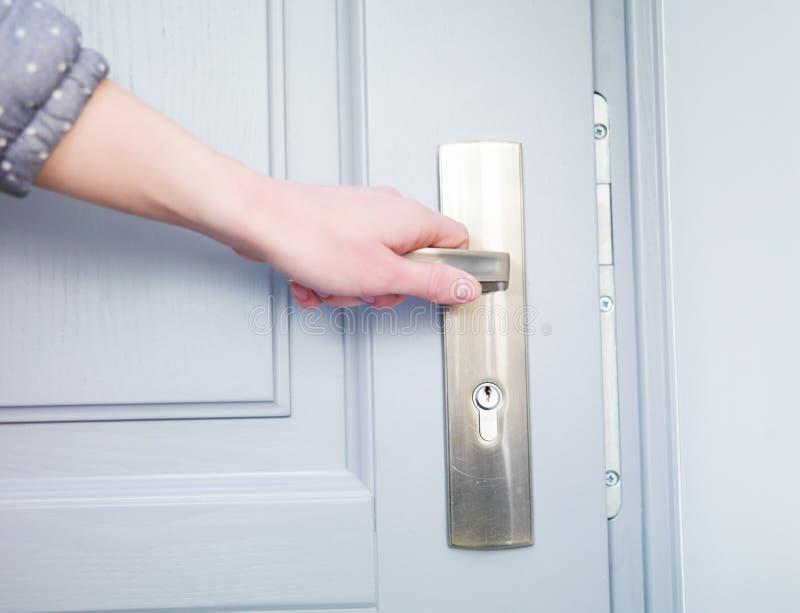 Hand och dörrhandtaget arkivfoto