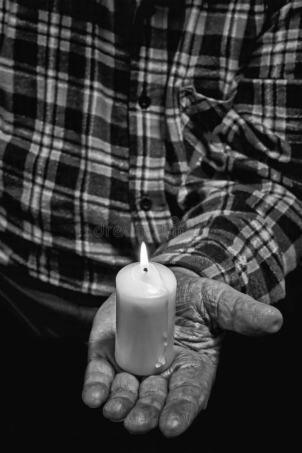 Hand och stearinljus arkivfoto