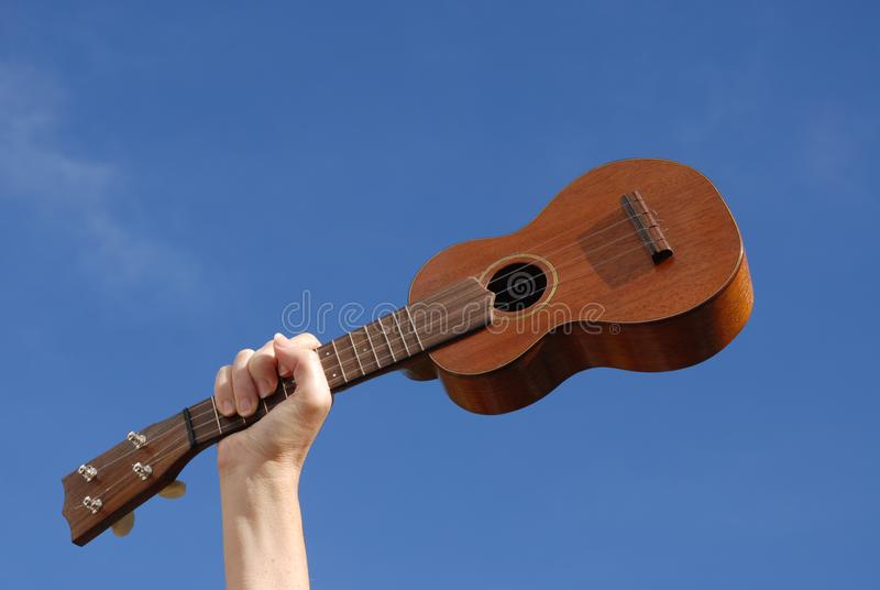 Hand och ukulele mot blå himmel royaltyfria bilder