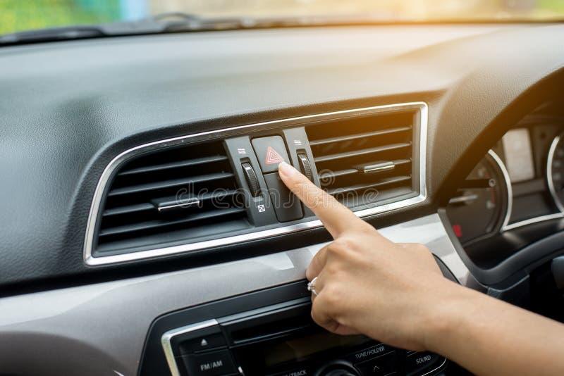 Hand- oder Fingerfrauenfahrerpresseauto-Notbeleuchtungsunterseite auf Armaturenbrett lizenzfreie stockfotos
