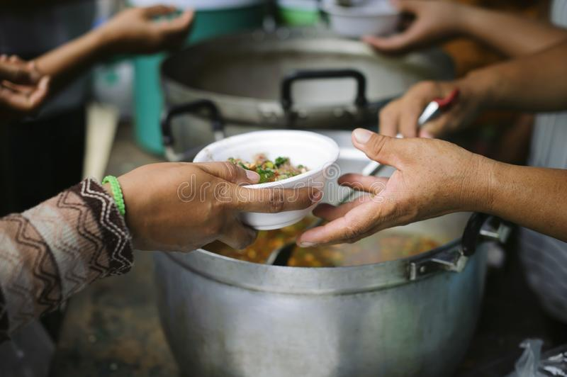 Hand offered to donate food from a rich man Share : The concept of social sharing : Poor people receiving food from donations :. Homeless people are helped with royalty free stock photography