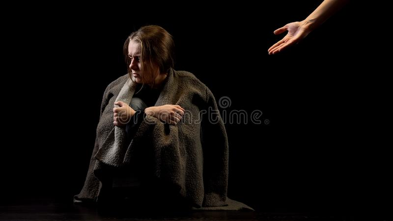 Hand offering help to miserable woman, support of domestic violence victim. Stock photo stock image