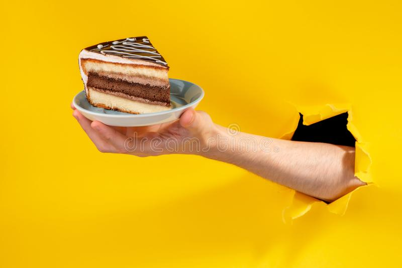 Hand offering a piece of cake through a torn hole in yellow paper background. stock photo