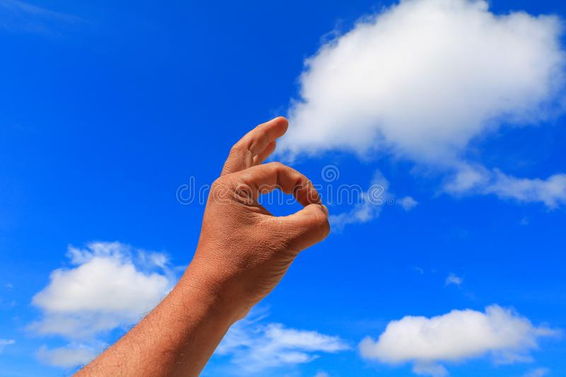 Hand ok sign on sky background stock photography