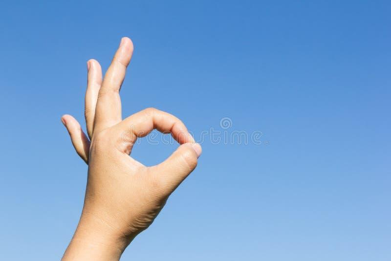 Hand ok sign on sky background stock photo