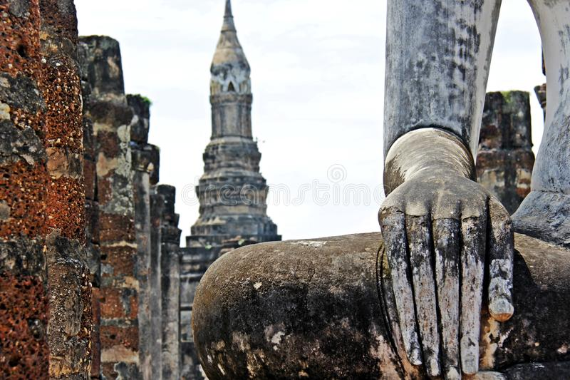 Hand of Old Buddha image and temple background at Sukhothai Thailand. Temple wat Buddhism religion peace peaceful antique background landscape stone travel stock photo